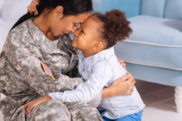 sweet loving family cuddling in a living room - armed forces stock photos and pictures