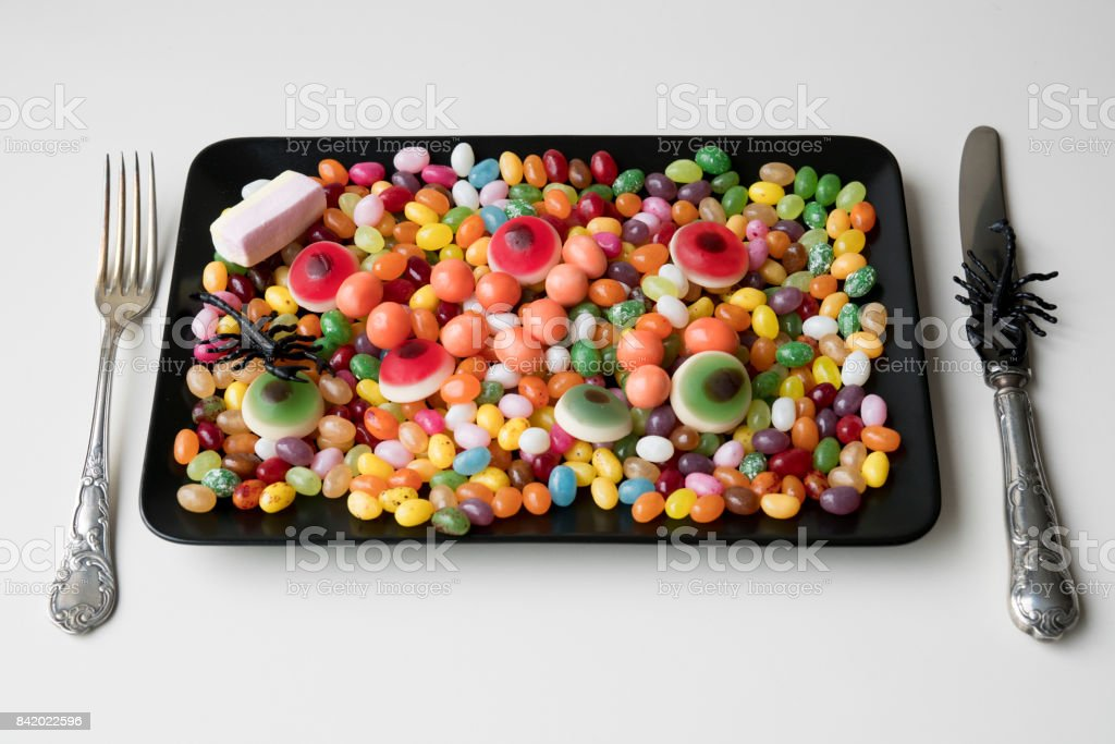 sweet lunch with mixed candy, jelly beans, eyes, on black plate stock photo