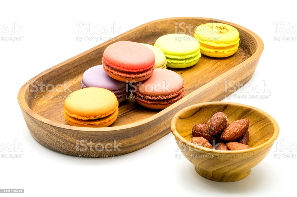 Sweet macarons in wooden tray and almonds in wooden bowl stock photo