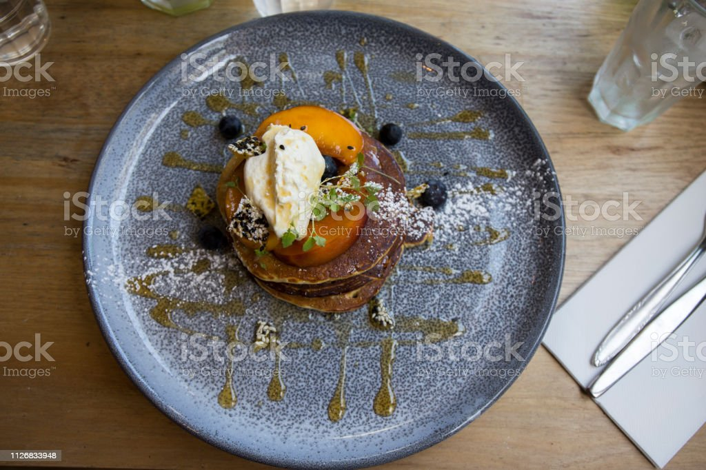 Sweet matcha pancakes with syrup and grilled nectarines stock photo