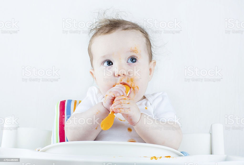 Sweet messy baby eating carrot in white high chair stock photo
