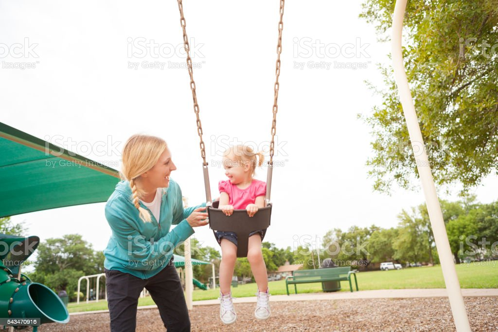 Sweet mom and daughter having fun on the swings stock photo