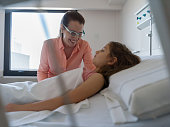 istock Sweet mom trying to cheer up her daughter lying down on hospital bed 1202156084