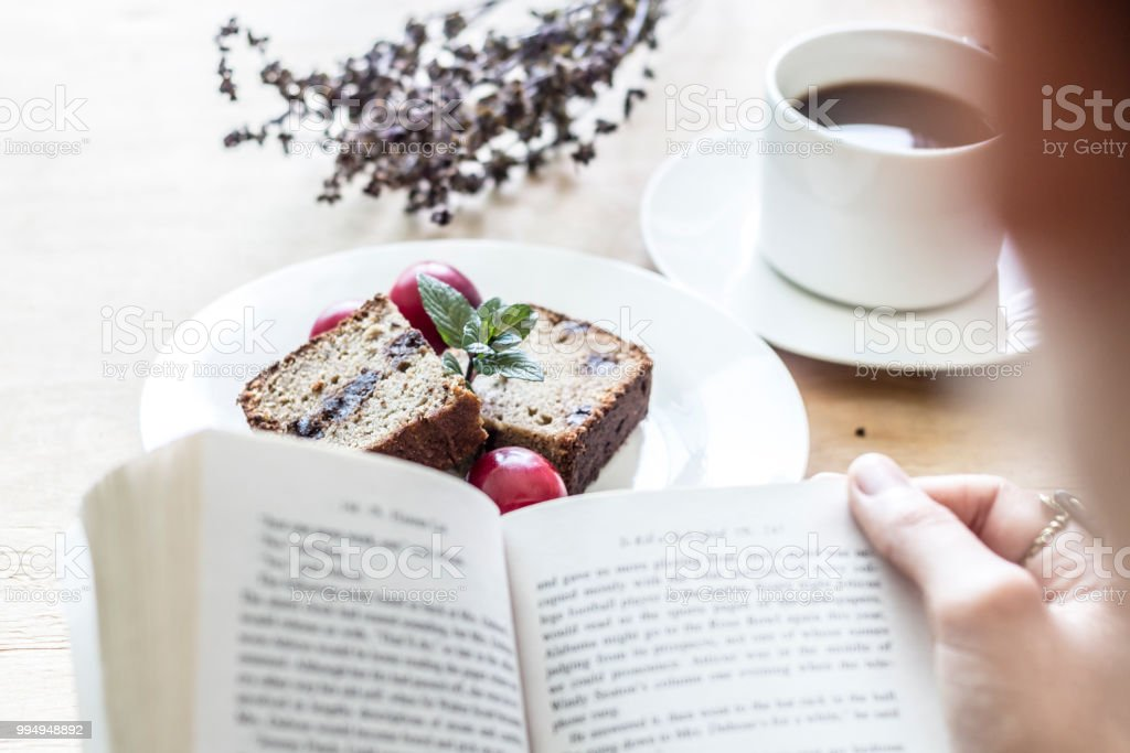Sweet morning flat lay with a coffee, a bread and a book stock photo