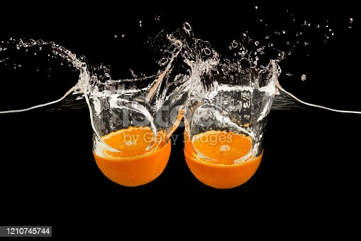 1169153675 istock photo Sweet orange halves falling into transparent water with splash on black background 1210745744