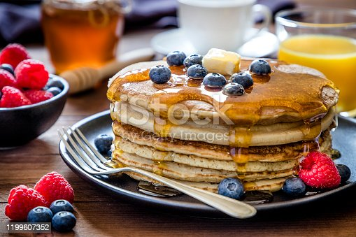 Front view of a stack of pancakes with blueberries and butter on top pouring honey on a black plate surrounded by a glass full os orange juice, a cup of coffee, a bowl with berries and a honey jar. Low key DSLR photo taken with Canon EOS 6D Mark II and Canon EF 24-105 mm f/4L