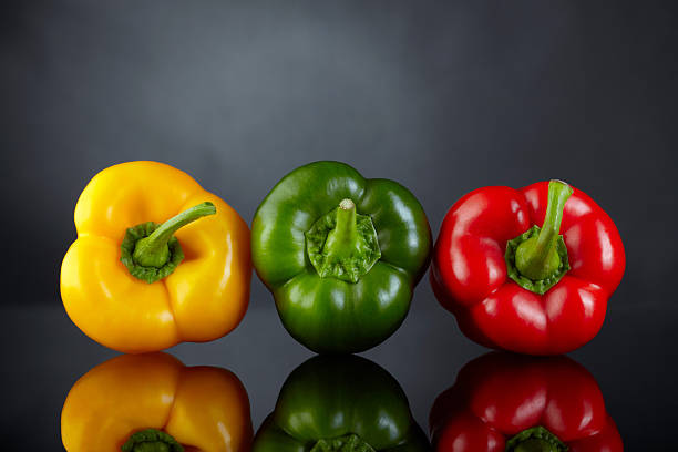 süßer paprika auf dunklem hintergrund - grüne paprikaschoten stock-fotos und bilder