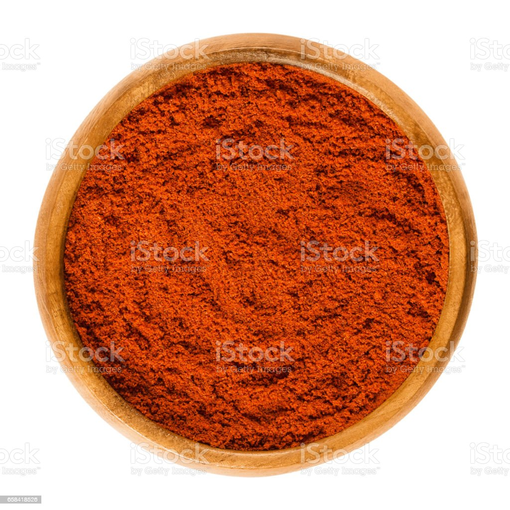 Sweet pepper red paprika powder in wooden bowl over white stock photo