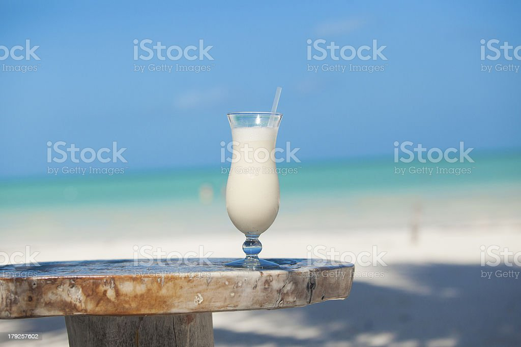 Sweet pina colada on the table in white beach stock photo