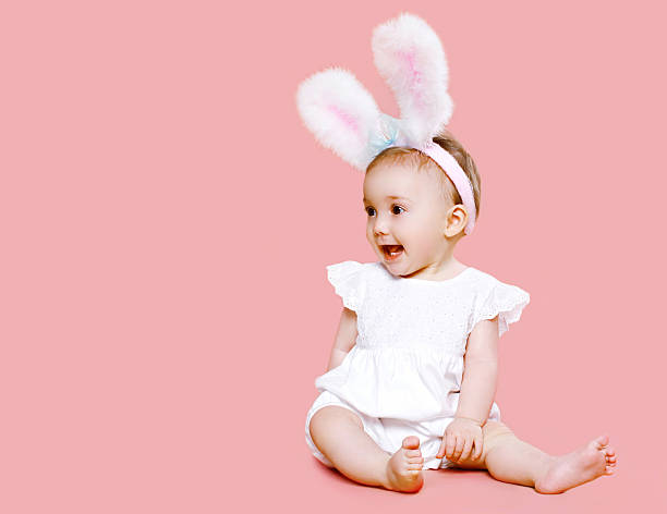 Sweet pink cute baby in costume easter bunny stock photo