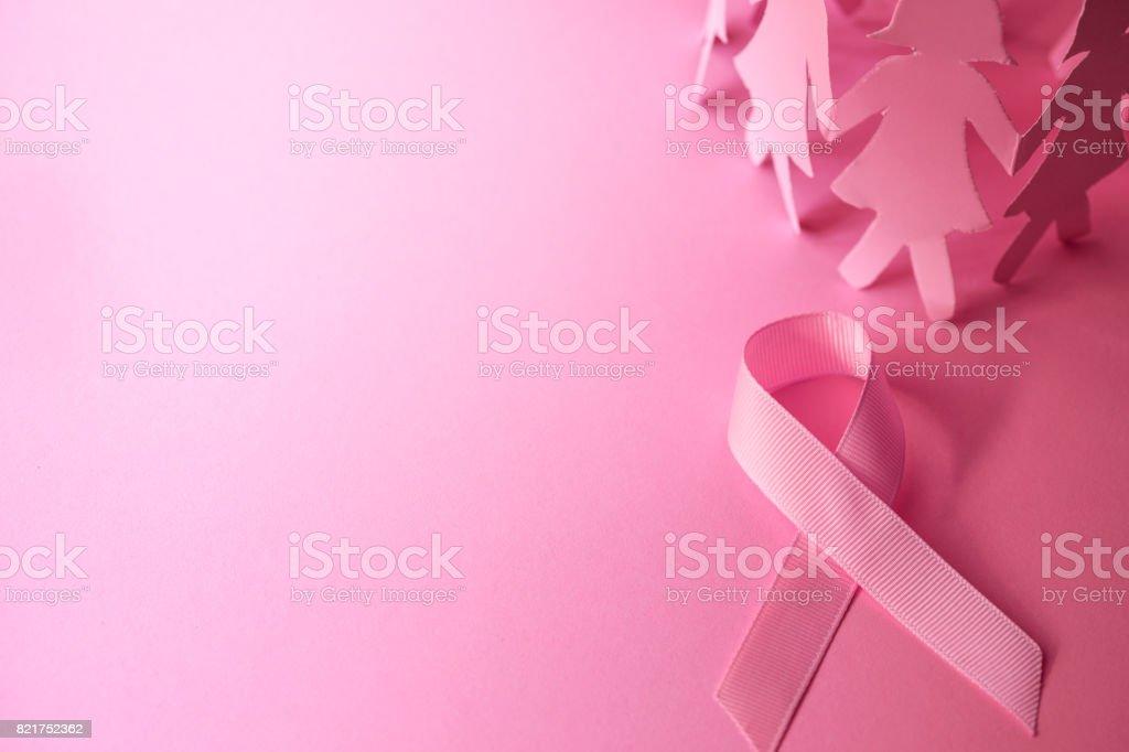 Forma de cinta de color rosa dulce con la muñeca de papel de la niña sobre fondo rosa símbolo de la conciencia del cáncer mama promover la campaña del mes de octubre - foto de stock