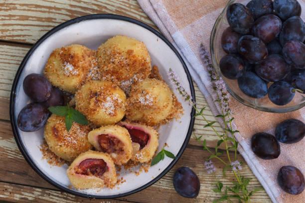 sweet plum dumplings in metal bowl on wooden table - dumplings stock photos and pictures