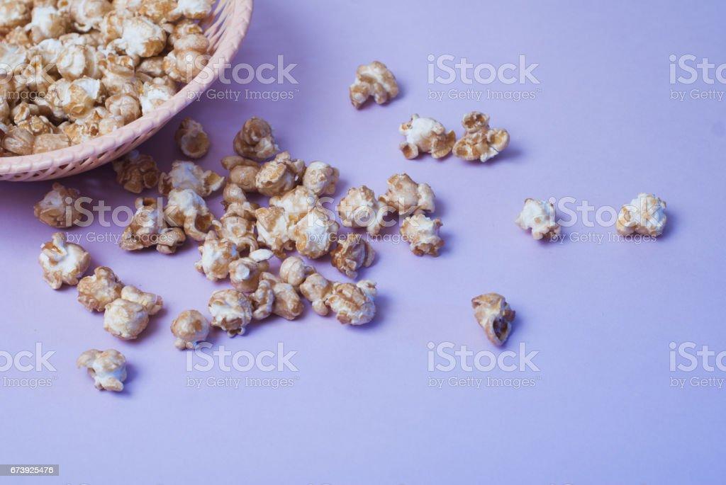 maïs doux dans un plat en osier sur un fond violet, photo libre de droits