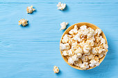 Sweet popcorn in a yellow bowl on a blue wooden background, top view