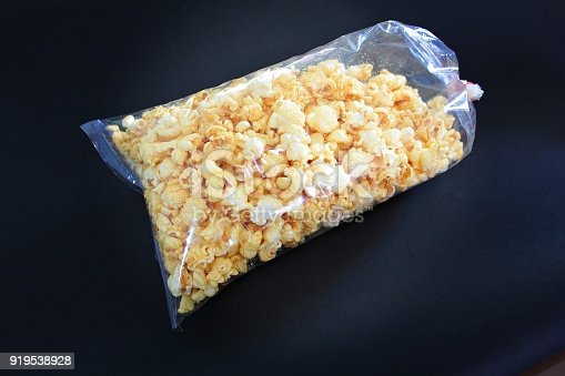 Sweet popcorn in transparent plastic bag, black background