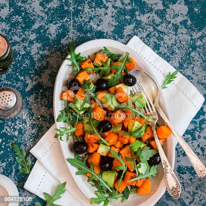 Sweet potato and avocado salad on blue background, top view