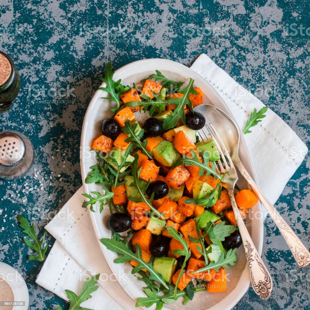 Sweet potato and avocado salad on blue background, top view stock photo