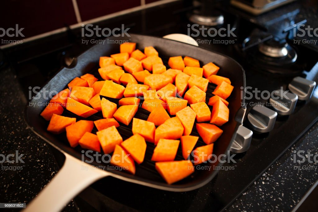 Sweet potato being cooked in a griddle pan/broiler stock photo
