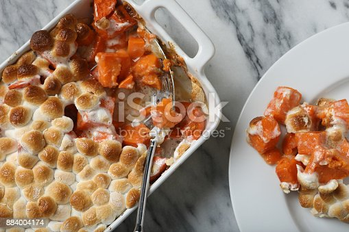 An overhead extreme close up horizontal photograph of  a Thanksgiving sweet potato casserole dish and a serving of the potatoes on a white plate.