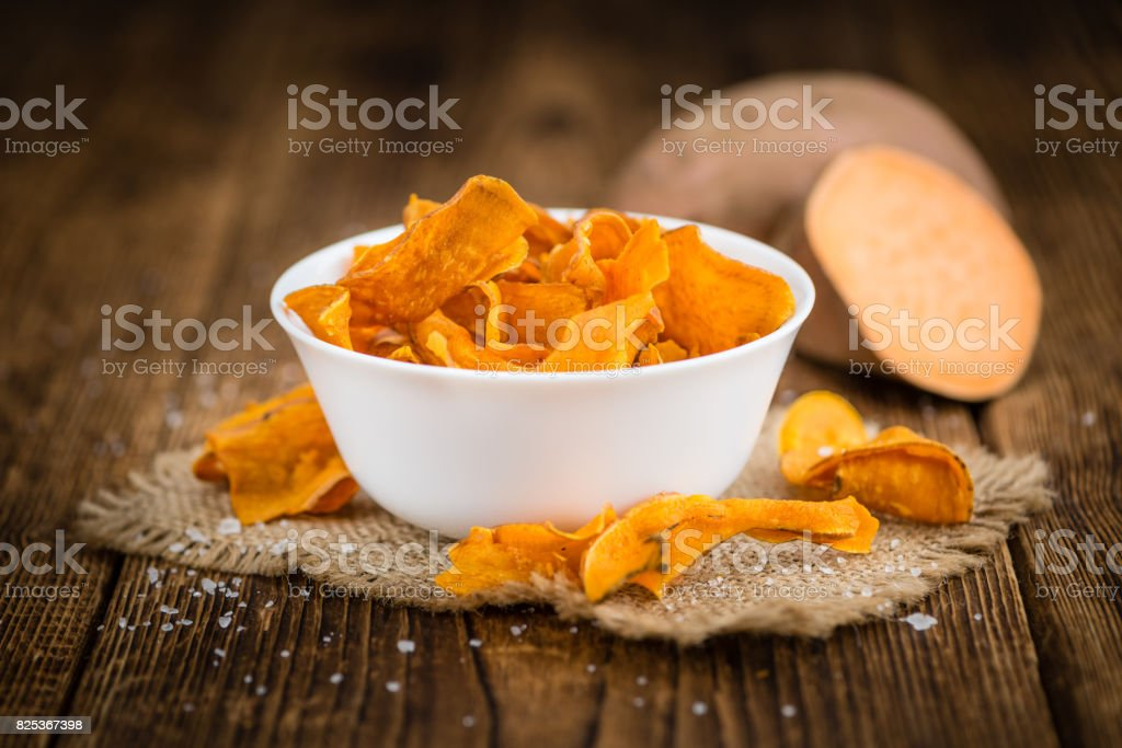 Sweet Potato Chips on wooden background; selective focus stock photo