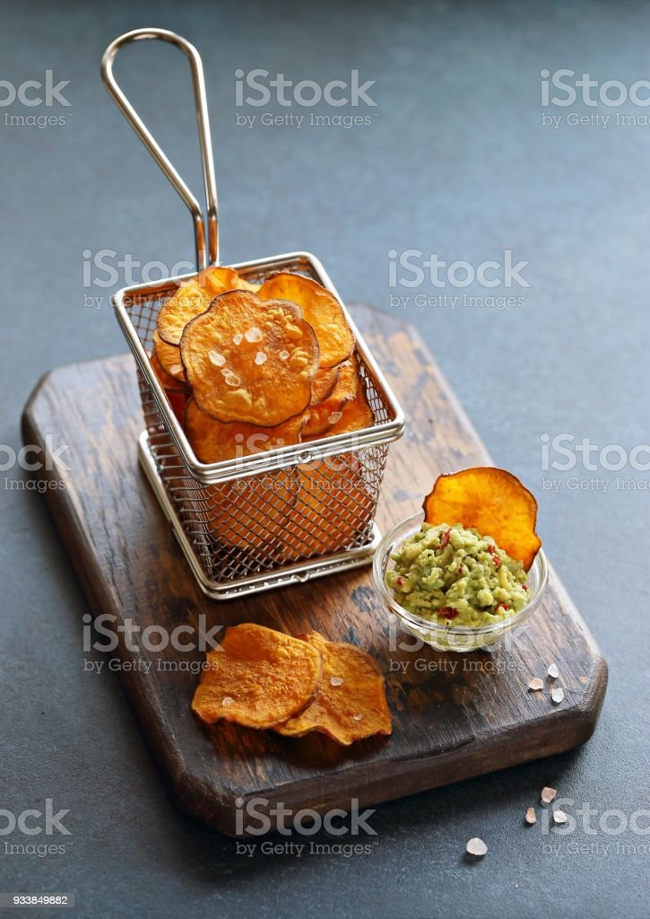 Sweet potato chips with avocado dip. stock photo