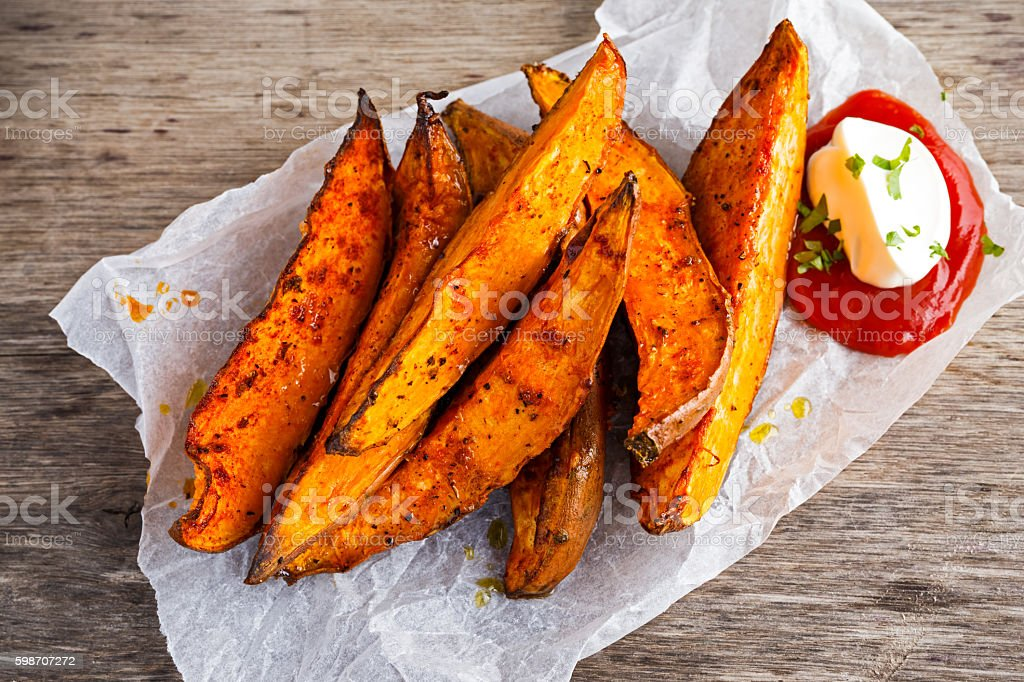 Sweet potato fries in paper wrap executed in metal serving stock photo