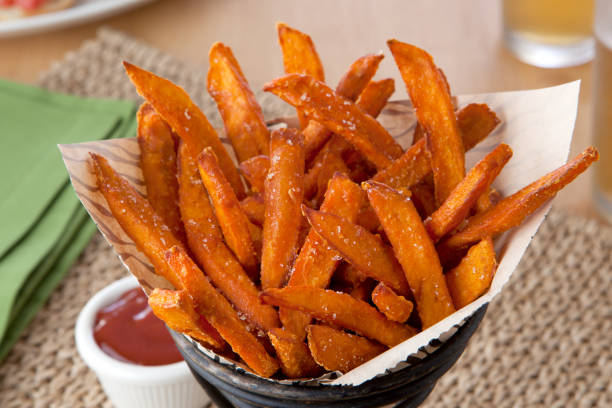 Sweet Potato Fries close up a basket of sweet potato fries sweet potato stock pictures, royalty-free photos & images