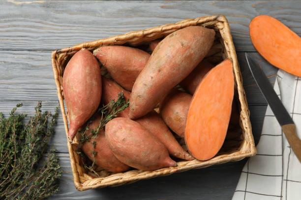 słodkie ziemniaki w koszu na drewnianym tle, widok z góry - słodki ziemniak zdjęcia i obrazy z banku zdjęć