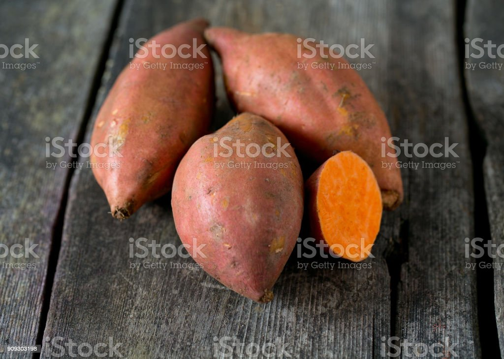 sweet potato on wooden surface - fotografia de stock