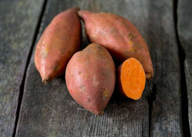 sweet potato on wooden surface sweet potato on wooden surface sweet potato stock pictures, royalty-free photos & images