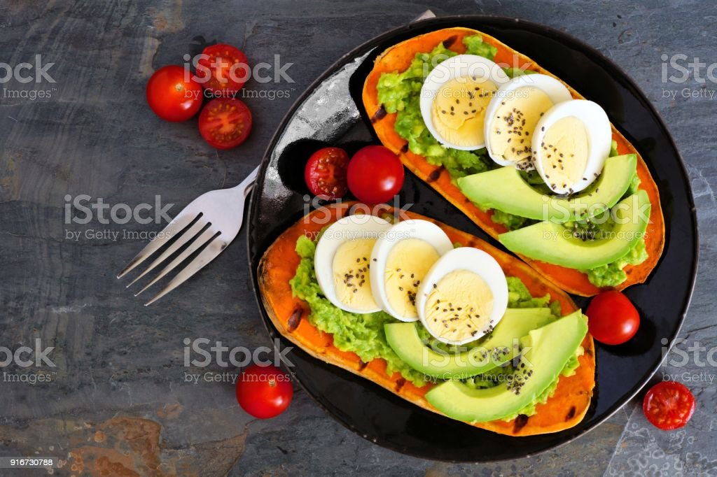 Sweet potato toasts with avocado, eggs and chia seeds over slate stock photo