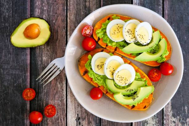 Sweet potato toasts with avocado, eggs and chia seeds over wood stock photo