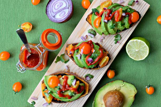 Sweet potato toasts with avocado stock photo