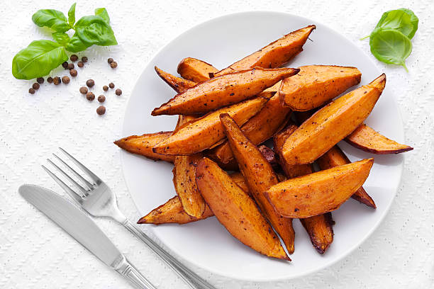 Sweet potato wedges Delicious homemade sweet potato wedges on a plate. sweet potato stock pictures, royalty-free photos & images