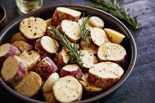 Raw sweet potato with rosemary, pepper and olive oil prepared for oven roasting