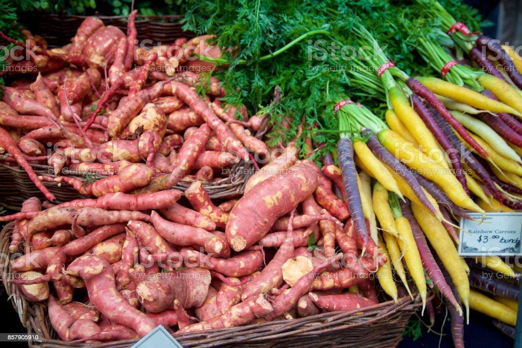sweet potatoes and heirloom rainbow carrots at the farmer's market stock photo