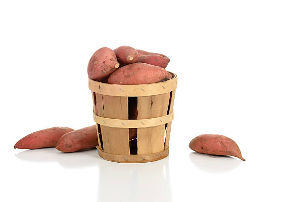 Sweet Potatoes in and Around a Basket stock photo