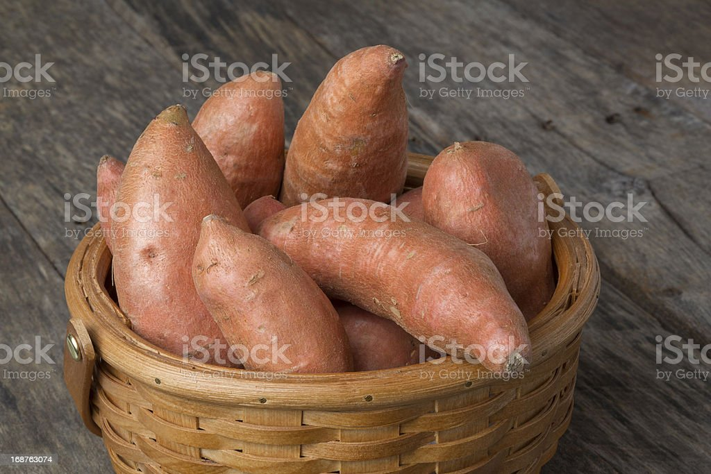 Sweet Potatoes in Basket on Wood Table royalty-free stock photo