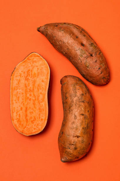 Sweet Potatoes on Orange Whole and halved sweet potatoes on an orange background. Sweet potatoes are a root vegetable rich in fiber and vitamins, and are available all year round. sweet potato stock pictures, royalty-free photos & images
