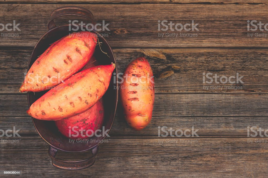 Sweet potatoes or yams in an old rustic tin container on a vintage rustic wood background with copy space. Top view or overhead composition. royalty-free stock photo