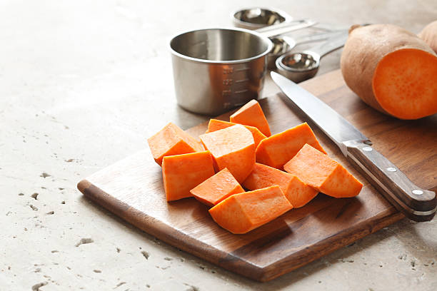 Sweet Potatoes preparation of sweet potatoes on cutting board. sweet potato stock pictures, royalty-free photos & images