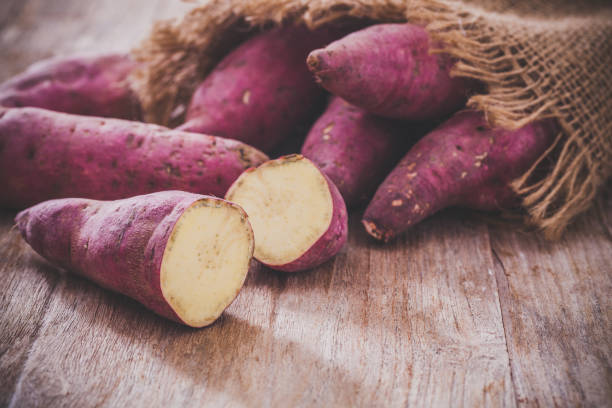 Sweet potatoes Raw sweet potatoes on wood background sweet potato stock pictures, royalty-free photos & images