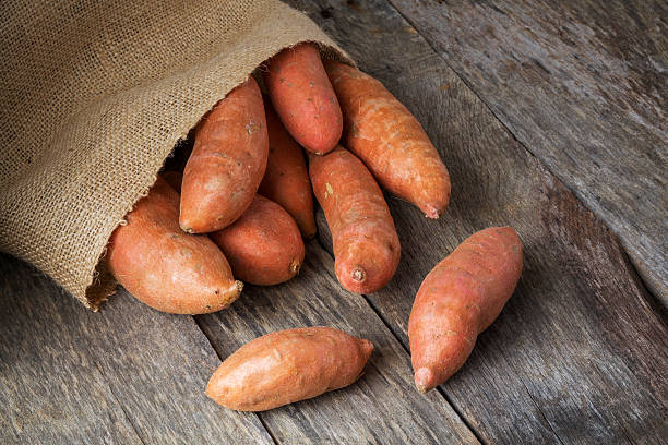 Sweet Potatoes Spilling From Burlap Bag stock photo