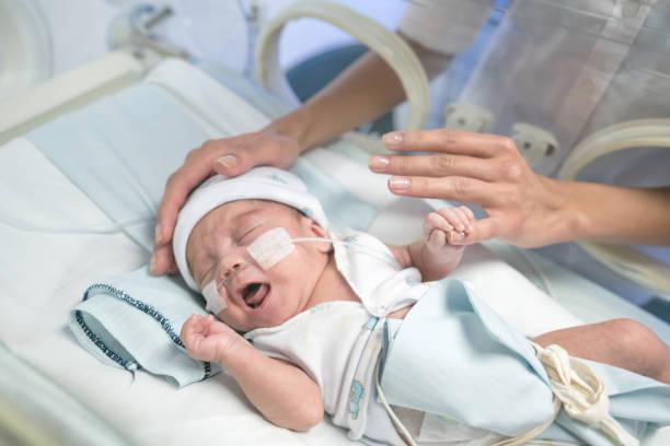 Süße Frühchen im Inkubator und unkenntlich Mutter streicheln Baby versucht ihn zu beruhigen – Foto