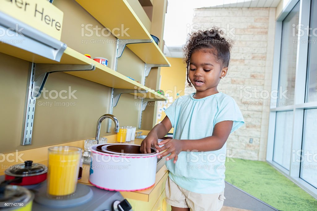 Sweet preschool girl playing with a pretend kitchen stock photo