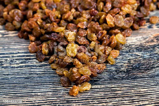 sweet raisins scattered on a wooden Board, obtained by dehydrating grapes, closeup