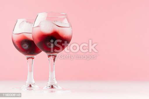 Sweet red alcoholic cocktails with ice cubes, blueberry in two goblets in soft light pink bar interior, copy space.