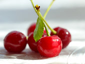 closeup sweet red cherry berry with green leaf on white background
