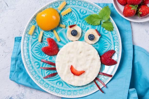 süßer reis waffeln mit joghurt in der form einer krabbe mit frischen früchten, essen für kinder idee, ansicht von oben - kochkunst stock-fotos und bilder