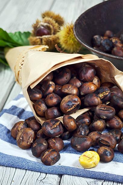 süße gebratene kastanien - heisse maroni stock-fotos und bilder